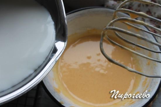 Тем временем горячее молоко вливаем в основу крема